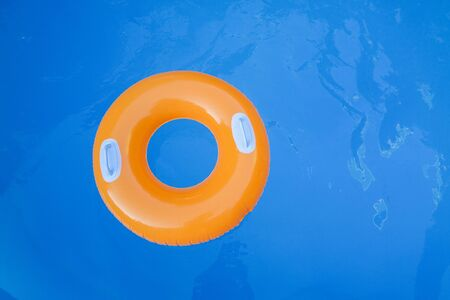 Children inflatable orange swimming ring with white handles floating in blue pool. Top view, close-up. Copy space for text.