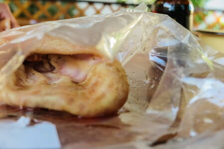 Smoked pork ear on on wooden background in package, offal. 写真素材