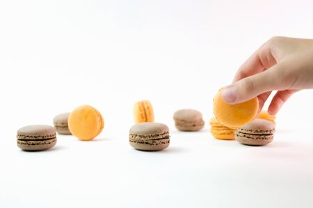 Macaroons on white background and hand holding one, colorful macaroons, selective focus. 版權商用圖片