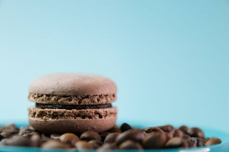 Macaroons on turquoise background with coffee beans, brown chocolate macaroons, selective focus.