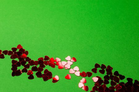 Glitter heart shapes in red on a green background can be used as a card background or Wallpaper for Valentines Day. Imagens