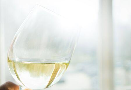 glass of white wine in female hand, selective focus. 版權商用圖片