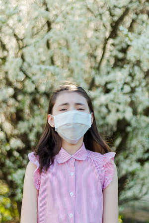 Allergy season. Young girl in medical mask against the blooming apple tree.