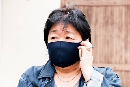 Protection of human face masks in a public place, prevention of coronavirus. Asian woman in a mask talking on a mobile phone.