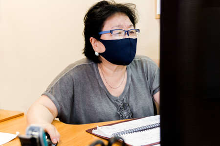 Protection of human face masks in a public place, prevention of coronavirus. Protection against the coronavirus pandemic, flu epidemic. An Asian woman aged about 65 years old in a mask poses.