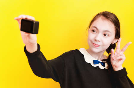 A young joyful schoolgirl girl takes pictures on a small camera on a yellow background. Selective focus. Foto de archivo
