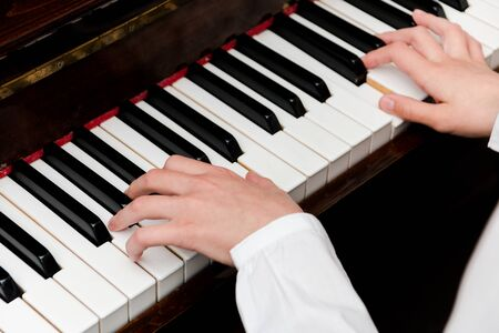 hands of a schoolgirl in a white shirt on the piano keys. selective focus.