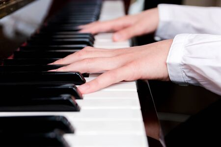 a schoolgirl in a white shirt plays the piano keys. selective focus.