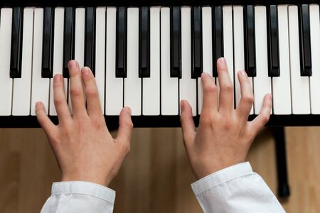 a schoolgirl in a white shirt plays the keys of a synthesizer. selective focus.