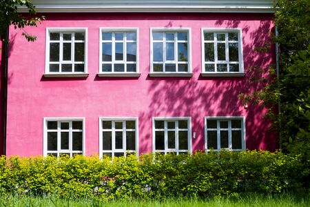A bright pink building with large Windows surrounded by bright green trees and shrubs. 版權商用圖片