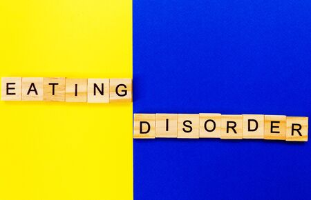 words eating disorder. Wooden blocks with an inscription on top on a yellow and blue background. Social problems of teenagers. 版權商用圖片