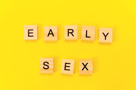 the words early sex. Wooden blocks with an inscription on top of a yellow background. Social problems of young people.
