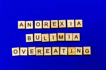 words anorexia, bulimia, overeating. Wooden blocks with an inscription on top on a blue background. Social problems of teenagers.