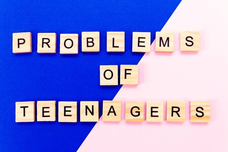Words problems of teenagers. Wooden blocks with an inscription on top on a yellow background. Social problems of teenagers. 版權商用圖片 - 148872845