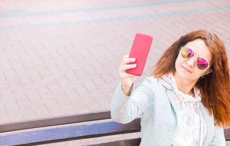 Red hair girl in sunglasses talking by mobile in city. Banner Foto de archivo