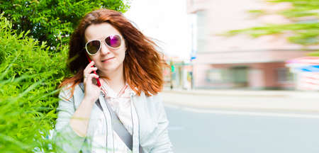Red hair girl in sunglasses talking by mobile in city. Banner.
