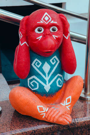 Street photo of a figure of a bright colored monkey holding a head of unusual color depicts various emotions. Moscow. Russia. June 2020. 新聞圖片