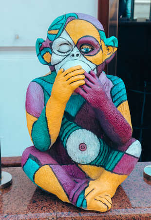 Street photo of a figure of a bright multicolored monkey with a closed mouth of unusual color depicts various emotions. Moscow. Russia. June 2020.