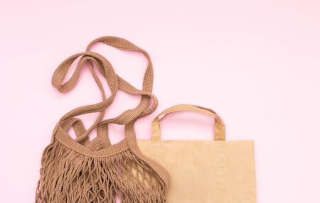 Reusable brown shopping bag and craft paper bag on pink background. Zero waste concept. No plastic.