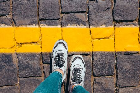 women's feet in white sneakers stand on the pavement one foot stepped on a bright yellow line, cross the line. 版權商用圖片