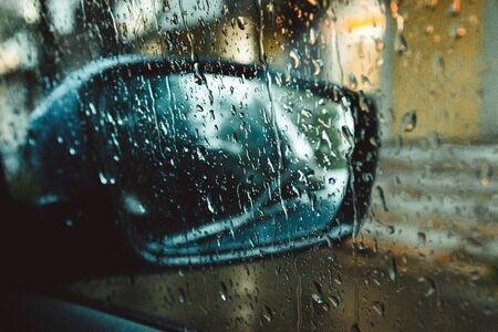Wet car mirror from the rain through the glass, raindrops close-up. Selective focus.