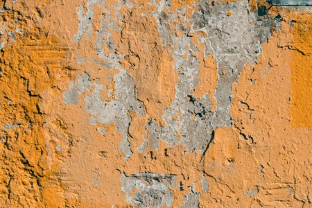 An old rural yellow wall with crumbling plaster, texture background. selective focus.