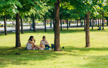 people eat fast food and relax in the Park after a working day in the summer. Moscow, Russia, June 2020.