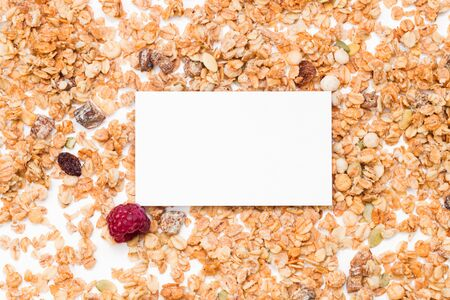 Crispy muesli with raspberry dry Breakfast and blank sheet of writing paper isolated on white background selective focus, top view.