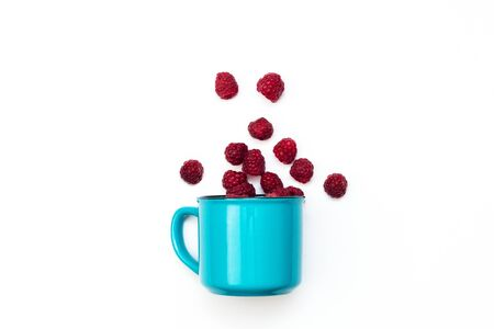 Juicy raspberry in blue mug isolated on white background selective focus top view.