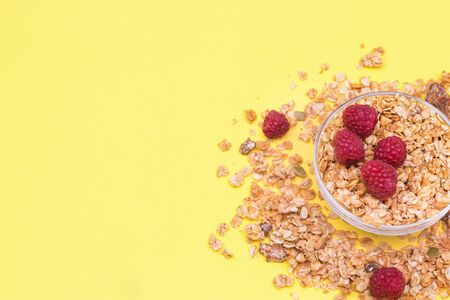 Crispy muesli with raspberry dry Breakfast isolated on yellow background selective focus, top view.