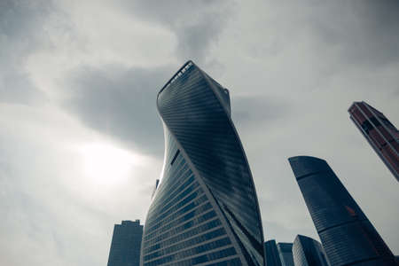 High modern glass tower of the Moscow city district for a business background against a cloudy dark sky. Moscow, Russia, June 2020.