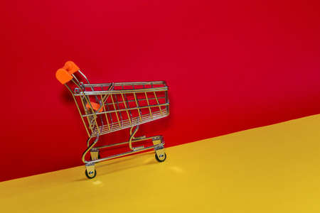 The desire to shop. Shopping cart on a red and yellow background. Minimalist style. Creative design. Shopping cart in a supermarket.