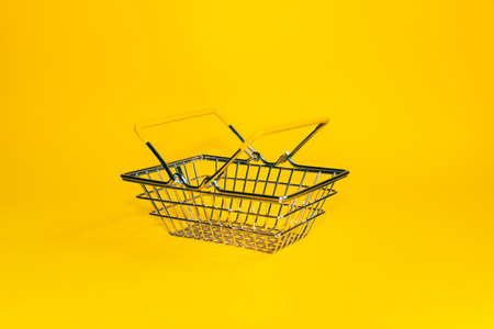 Buying concept. Shopping cart on a yellow background. Minimalist style. Creative design. Shopping cart in a supermarket.