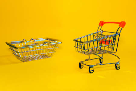 The concept of purchase. Cart and shopping basket on a yellow background. Minimalist style. Creative design. Shopping cart in a supermarket. Foto de archivo