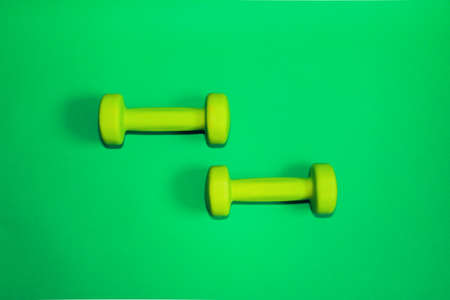 Green dumbbells isolated on a green background. Flatlay concept of fitness, gym and healthy lifestyle. The view from the top and copy space. 版權商用圖片