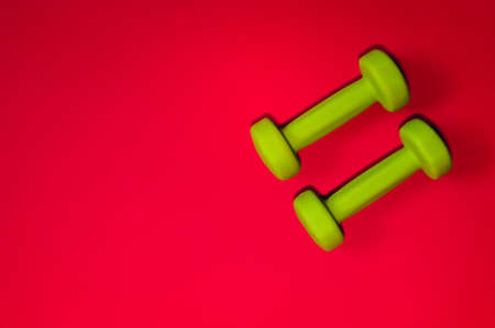 Green dumbbells isolated on a red background. Flatlay concept of fitness, gym and healthy lifestyle. The view from the top and space for copy.