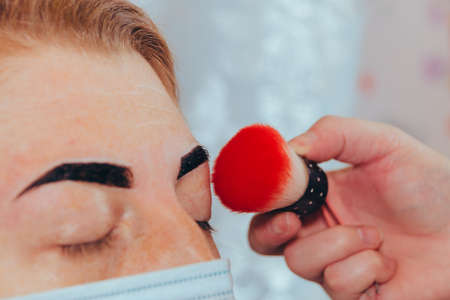 Beauty treatment. Correction and coloring of the eyebrows, shaping the eyebrows, removing hair with wax. Selective focus.