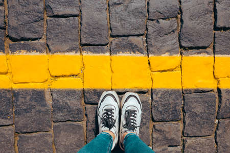 women's feet in white sneakers stand on the pavement behind the yellow line, body parts do not cross the line.
