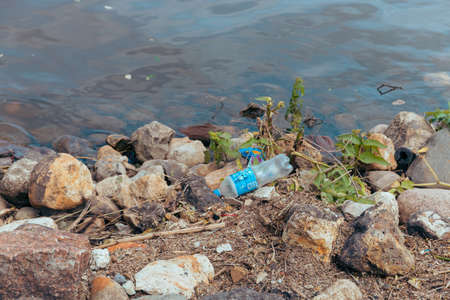 Environmental pollution ecological problem. RiverBank polluted with garbage. Moscow, Russia, June 2020.