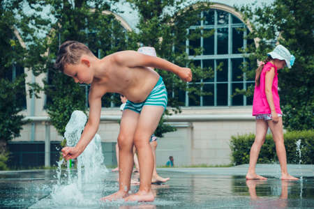 Hot summer weather, unknown small children bathe in the city fountain in the park. Moscow, Russia, July 2020.