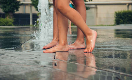 Hot summer weather, small children's feet bathe in the city fountain. Selective focus.