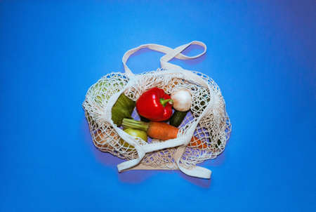 Eco friendly cotton shopper and reusable mesh shopping bag with vegetables on blue background. Selective focus.