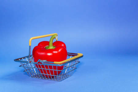 food basket with pepper on blue background. Selective focus.