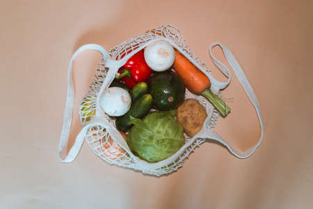 Eco friendly cotton shopper and reusable mesh shopping bag with vegetables on light background. Selective focus.