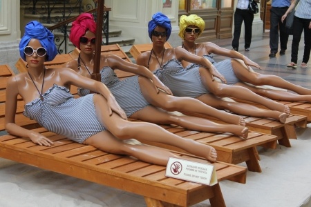 Models of seminude women lie on the sidewalk