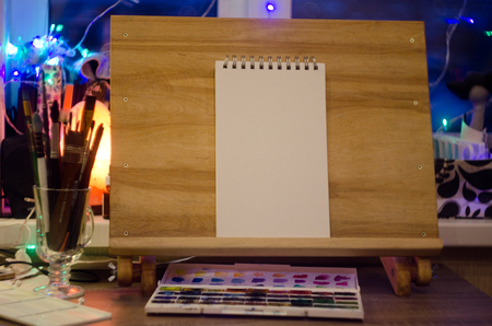 mocup artist easel sketch picture bokeh evening. Wooden easel in the room