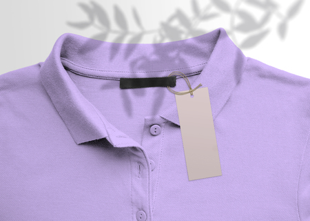 Clothes label tag on cloth background. Branding template mockup on violet fabric background polo shirt