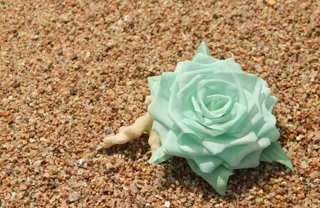 Beautiful hand made mint cotton flower on sand. Vintage retro style decoration. Fashionable female corsage brooch and barrette Archivio Fotografico - 130856133