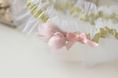 Bridal garter with silk flowers piones. Elegance wedding day celebration of love and marriage. Soft focus Stock Photo