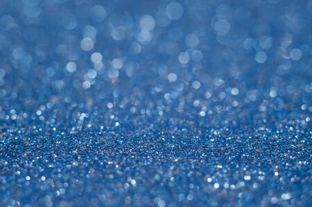 Classic Blue color. Color of the year 2020. Abstract festive bokeh background with shining defocus sparkles. Blurred glitters shimmering dust macro close up, copy space for text logo. De-focused Stock Photo